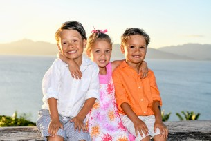 Triplets seated against the sunset smile at the camera in Fiji family vacation