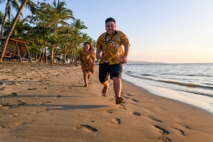 Brother and sister run and play on the beach at Double Tree Hilton Fiji