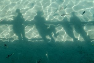 The family creates shadows into the clear waters at Plantation Island Resort
