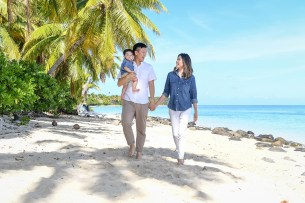 The family strolls on the white sand beach against green palm trees and blue sea