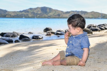 The cute little boy puts the coral rock in his mouth at Plantation Island Resort Fiji