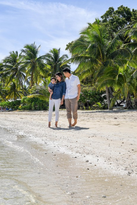 The family strolls ahead of lofty green palm trees at the Plantation Island Resort Fiji