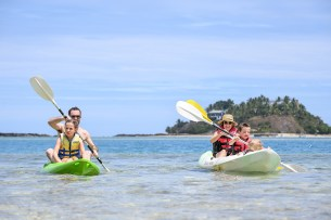Mother and son, father and daughter canoe together at Malolo Island Resort
