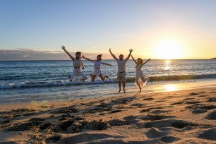 The family leap frogs against the sunset at Fiji