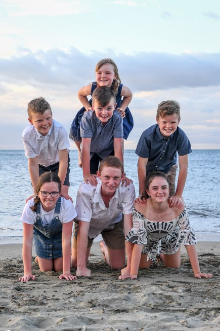 Cousins build a human tower on the beach at Natadola beach Fiji