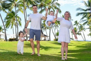 Mother and father lift baby off the ground against palm trees