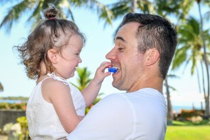A baby daughter feeds her father a toy