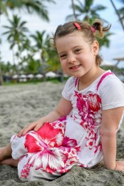 A cute girl in a red dress posses seated on the beach