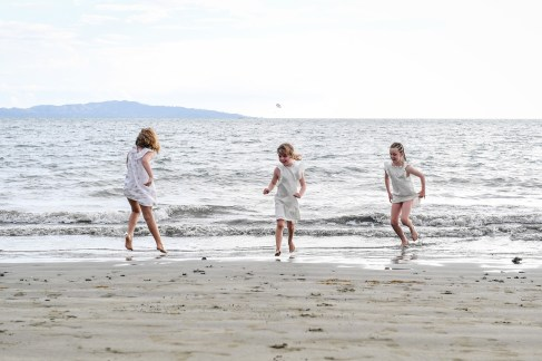Cousins in white kick around on the beach in the sand