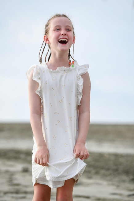 Cute caucasian girl in braids laughs on the beach