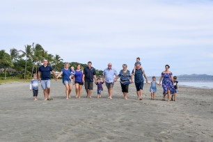 An extended family holds hands while walking on the beach