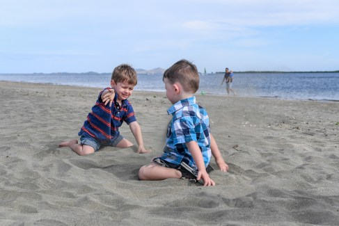 Two brothers playing with sand on the beach