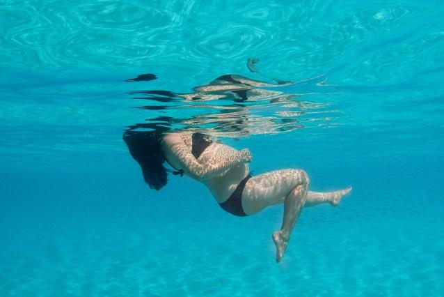 Fish fall behind as a lady kicks her legs in underwater pregnancy shoot