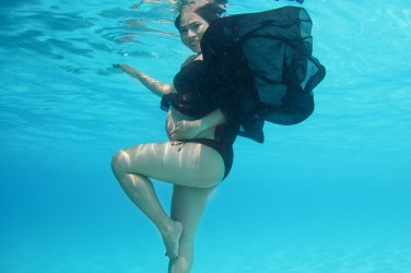 Lady in black smiles at the camera underwater with her black dress floating behind her