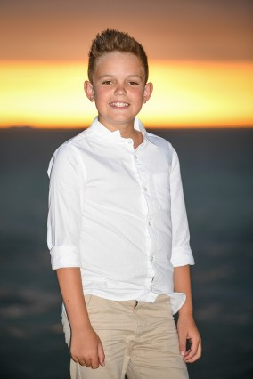 Portrait of a boy standing at the beach at sunset in Fiji