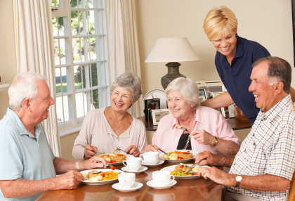 Group Of Senior Couples Enjoying Meal Together In Care Home With Home Help