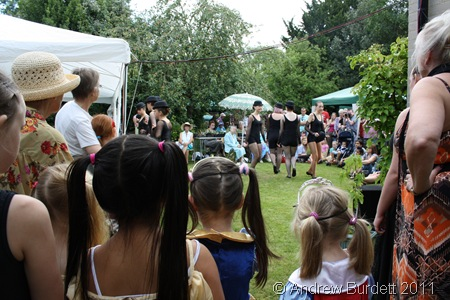 WATCHING FROM THE SIDE-LINES_Younger dance school students watch as their older friends perform a routine in front of the crowd.