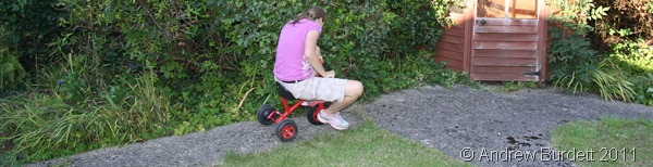 ONE LAST RIDE_Harriet taking the trike down to the end of the garden.