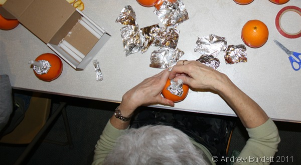 STICK A CANDLE IN IT_A volunteer fits candles and wax-catching foil to the oranges.