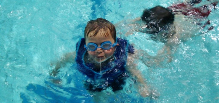A child wearing a buoyancy-aid swims with his older brother.
