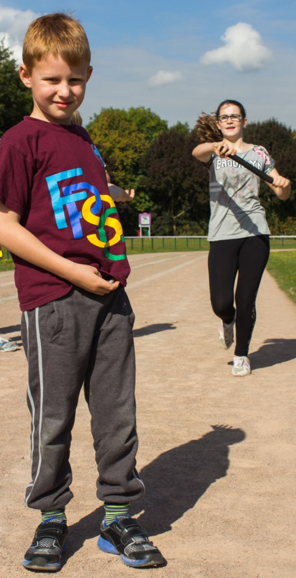 A Furze Platt Scout passes the baton on to a fellow runner.