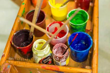 Image of paint brushes and pots in school art