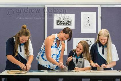 Teacher assisting students with pottery in art class