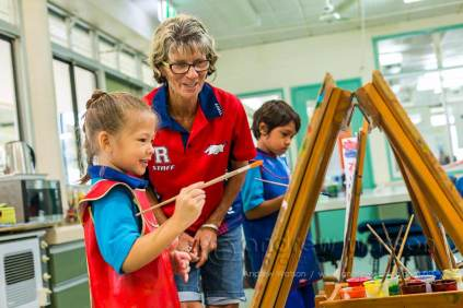 Teacher assisting young student with painting in art class