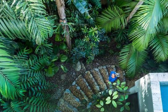 Image of woman walking through residential tropical garden in Port Douglas