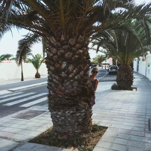 Planet Surfcamps Fuerteventura Anna versteckt sich hinter einer Palme