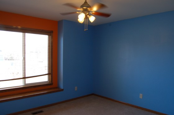 The front bedroom when we moved in - bright blue walls, bright orange accents, a too-tiny fan, and PLENTY of colorful paint on the carpet.
