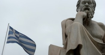 A Greek flag flies next to a statue of a