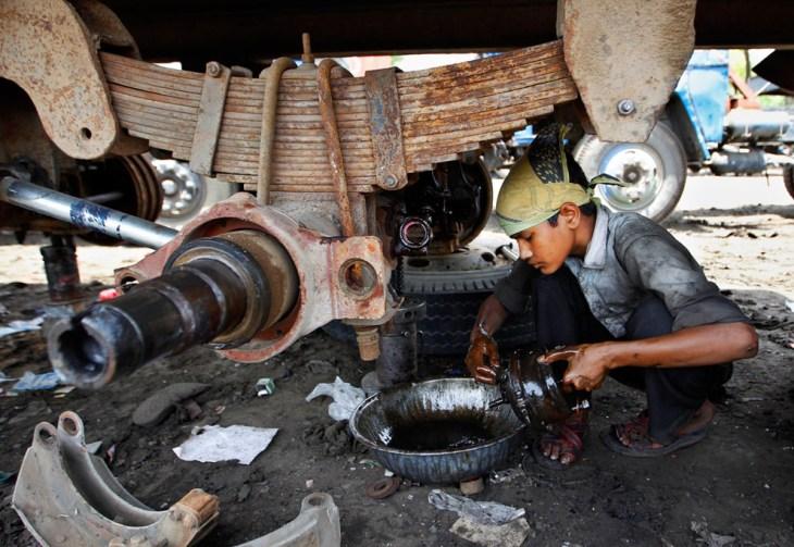 Ένα νεαρό αγόρι καθαρίζει τμήματα ενός φορτηγού στο Νέο Δελχί, Ινδία