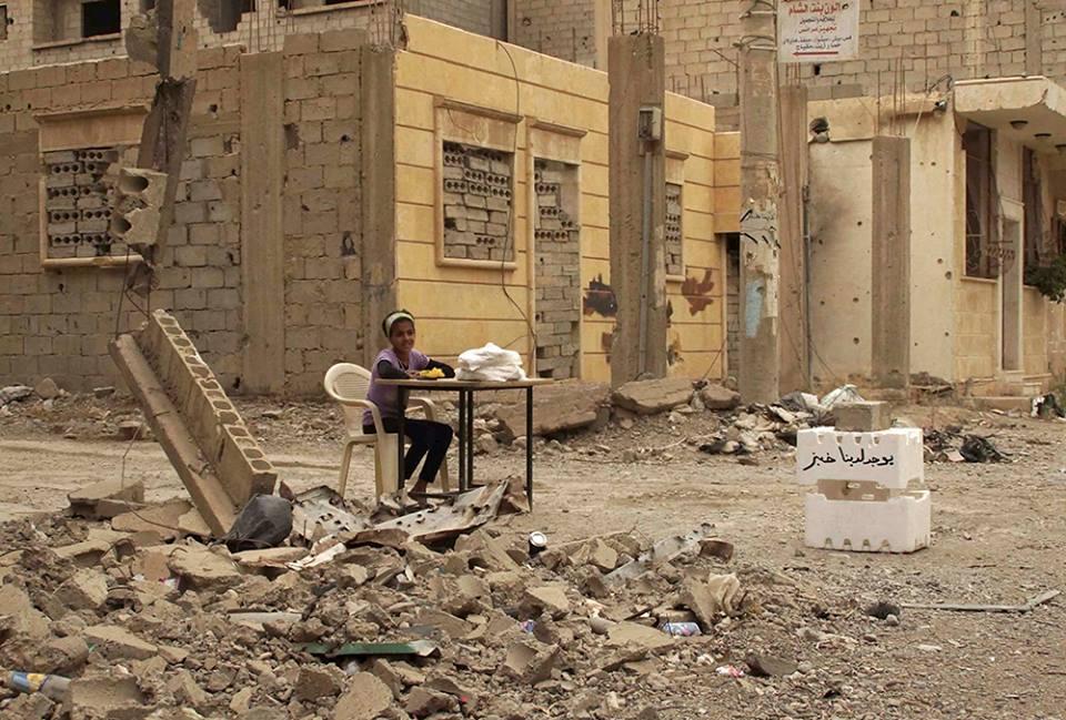 Συρία. Ένα κορίτσι πουλάει ψωμί ανάμεσα στα ερείπια στη πόλη Ντέιρ αλ-Ζορ. 9 Μαΐου 2013.