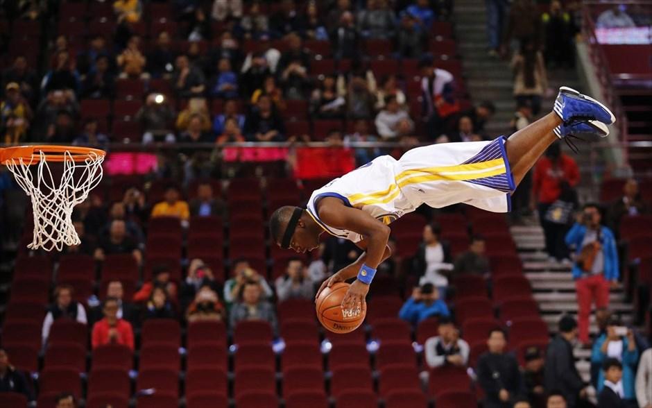Μέλος της ακροβατικής ομάδας Flying Dubs της ομάδας του NBA Golden State Warriors, εκτελεί ένα νούμερο πριν τον αγώνα εναντίον των Los Angeles Lakers για το στο NBA Global Game Πεκίνο.