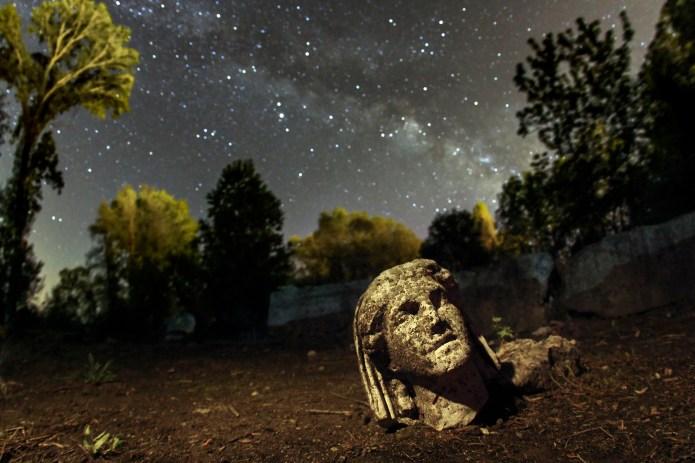 Δίον. Για να φωτογραφίσει το άγαλμα με φόντο τον Γαλαξία ο Λουκάς χρειάστηκε να σκάψει μια μικρή λακκούβα για να τοποθετήσει την κάμερά του όσο πιο χαμηλά γινόταν.