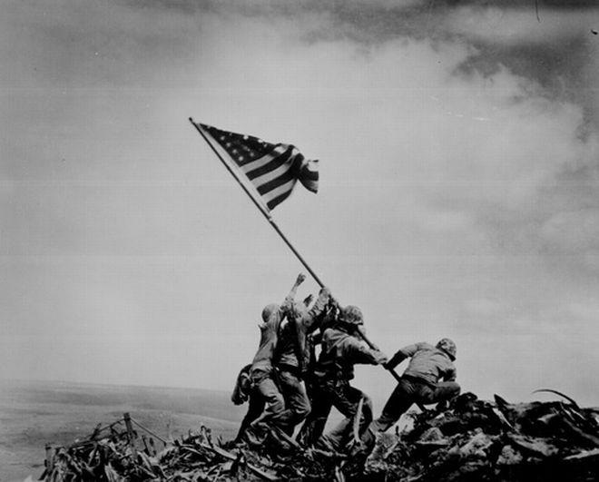 Iwo Jima-23 Φεβρουαρίου 1945: Έξι Αμερικανοί πεζοναύτες τοποθετούν μια σημαία κατά τη διάρκεια της μάχης στην Iwo Jima. Τρεις από αυτούς τους άνδρες, σκοτώθηκαν αργότερα στη μάχη. Η συγκεκριμένη εικόνα θυμίζει το τέλος του Β Παγκοσμίου Πολέμου και ενέπνευσε την κατασκευή του περίφημου μνημείου στην Ουάσιγκτον.