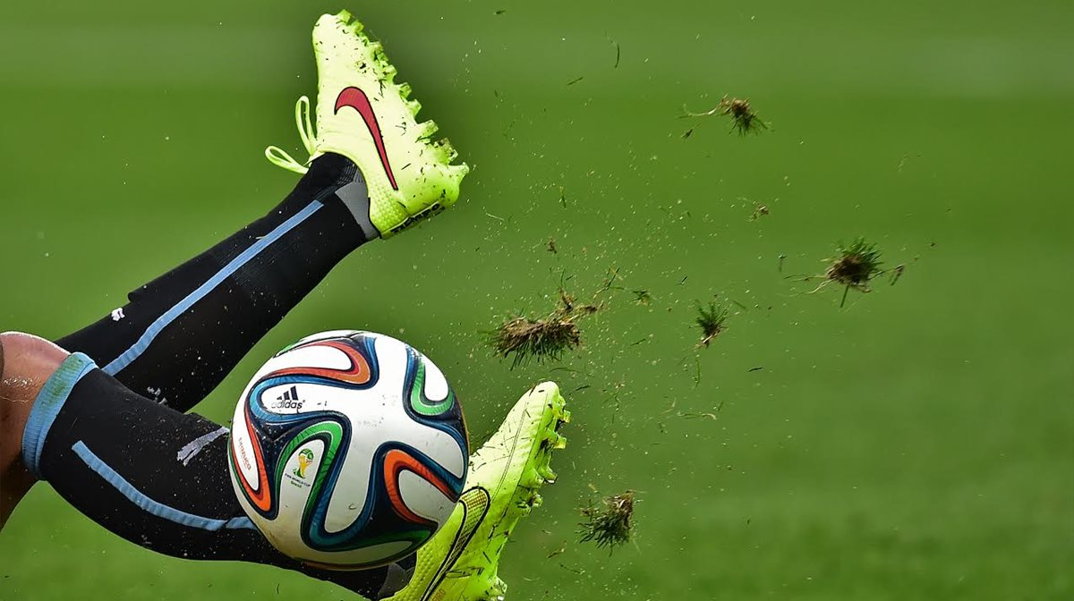 Καλλιτεχνικό φωτογραφικό στιγμιότυπο από τη μάχη ποδοσφαιριστή με τη μπάλα, αλλά και με το... γρασίδι σε ματς για το Παγκόσμιο Κύπελλο.