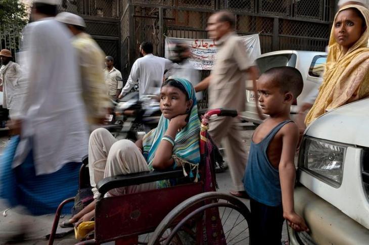 Άνθρωποι περνούν δίπλα από την 13χρονη Χουνούπα Μπέγκουμ που είναι τυφλή τα τελευταία δέκα χρόνια και ζει στο Νέο Δελχί. Η μικρή αναγκάζετε να ζητιανεύει και αυτό είναι το μόνο εισόδημα της οικογένειας της. Δίπλα της στέκεται ο εξάχρονος Σείχ που έχει πρόβλημα στον κεφάλι τους καθώς έχουν συσσωρευτεί υγρά και από πίσω είναι η 30χρονη μητέρα που πάσχει από άσθμα. Ο πατέρας πέθανε πριν από δέκα χρόνια ενώ το αναπηρικό καροτσάκι το χάρισε στην οικογένεια ένας περαστικός.