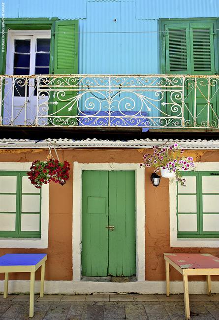Λευκάδα: Πέτρα στο ισόγειο λαμαρίνα στον όροφο ττα πολύχρωμα σπίτια της πόλης που εκτός από κουκλίστικα είναι και αντισεισμικά