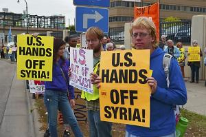 Protestors, from left to right, Sasha Pevzner, Eric Hefty and Victor Roberts hold signs during an anti-intervention in Syria rally Saturday in Minneapolis. (Pioneer Press: Andy Greder)