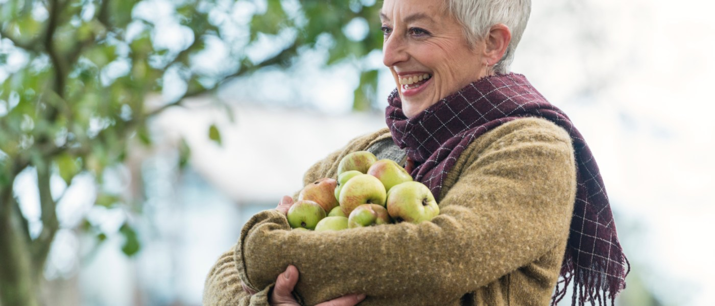 Happy senior woman with armful of apples