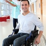 An image of a young man in a wheelchair happy to receive physiotherapy