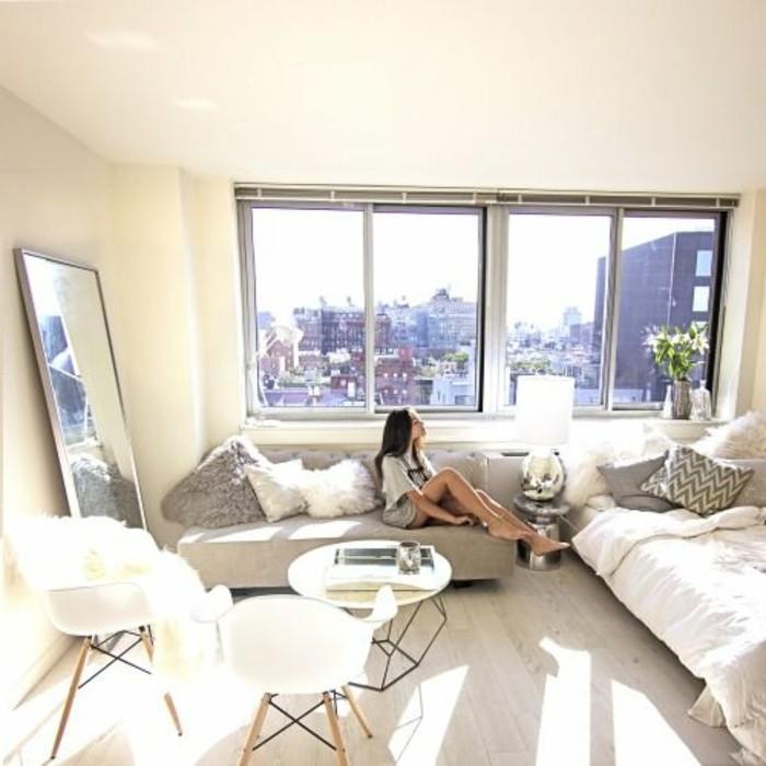 Salon avec canapé gris, sol en bois beige clair, murs beige, grande