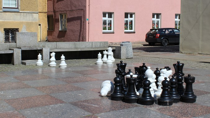 A giant public chessboard made of marble with most chess pieces collected in one cluster in Klaipeda.