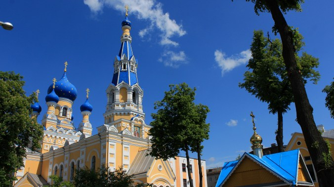 A colorful Orthodox church with yellow walls and blue domes in Brest, Belarus.