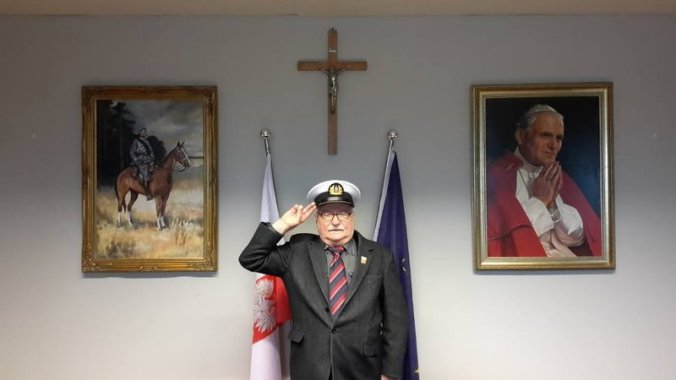 Why Poland is awesome?Lech Wałęsa posing in front of the cross and a painting of Pope John Paul II