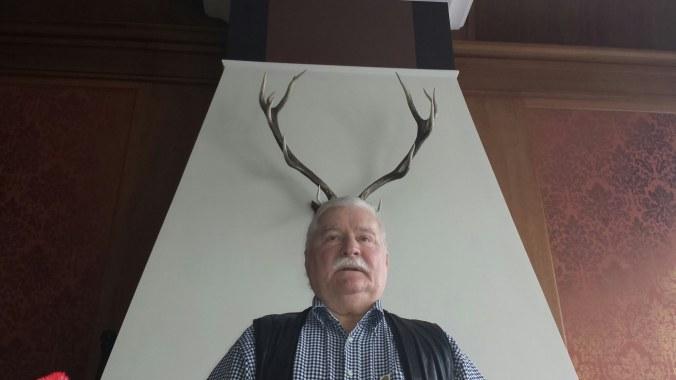 President Lech Wałęsa posing with deer or moose horns behind his head.