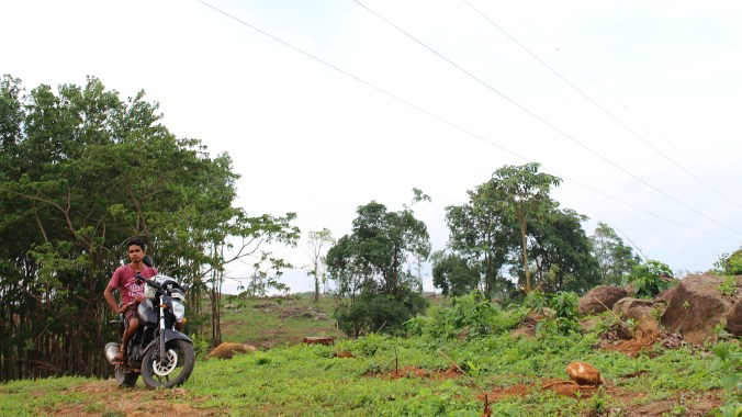 A young man from Kerala posing in a green hill with a motorcycle.