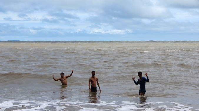Three young Indian men swimming at Om Beach and posing for the camera.